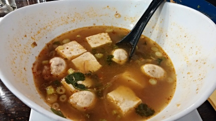 A big bowl of Tom Yum soup with tofu